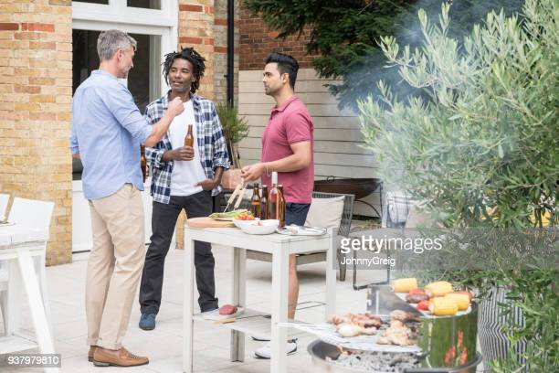 Three men drinking beer on patio with barbecue