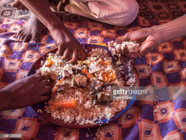 three men eat thieboudienne with their hands together from one plate - exotismo fotografías e imágenes de stock