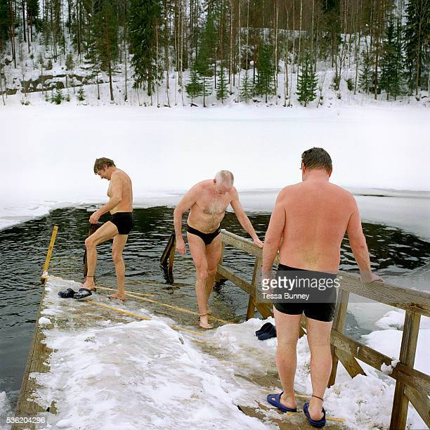 Three men going ice swimming after a sauna at the small lake of Vuorilampi Jyvaskyla Central Finland Ice swimming takes place in a body of water with...