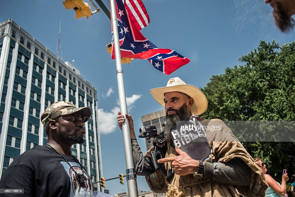 Three men have a peaceful but passionate conversation on the grounds of the South Carolina state house July 9, 2015 in Columbia, South Carolina. Later in the day, Governor Nikki Haley signed a bill removing the Confederate battle flag from the state house grounds.