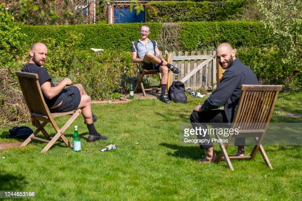 Three men having a socially distanced chat in a garden, during Covid-19 lockdown period, UK.