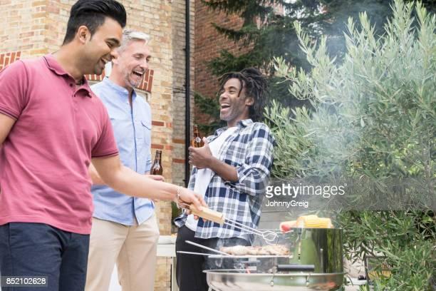Three men having bbq in garden with beer
