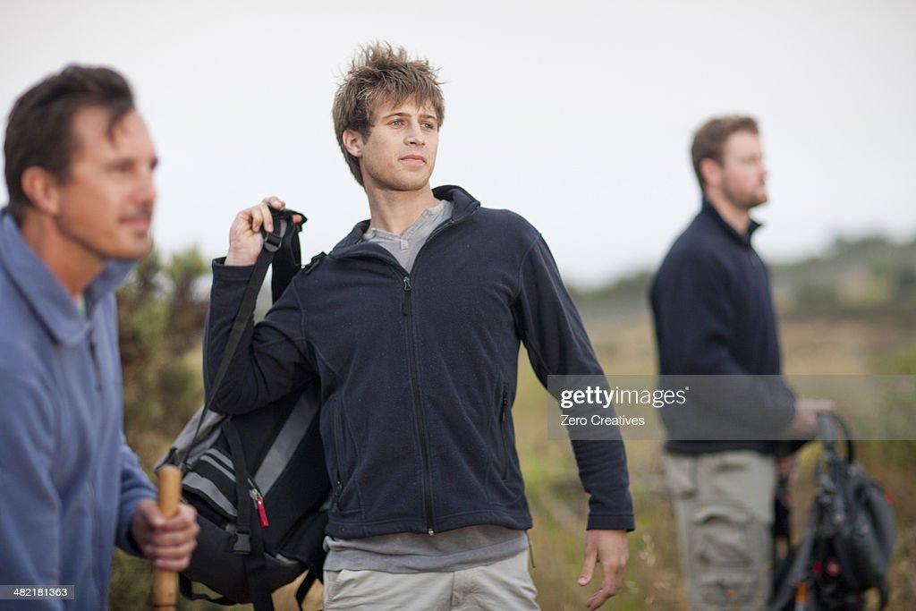 Three men hiking in rural landscape : Stockfoto