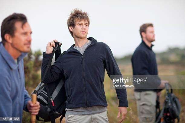 Three men hiking in rural landscape