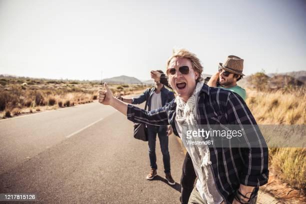 three men hitchhiking at a country road - straßenrand stock-fotos und bilder