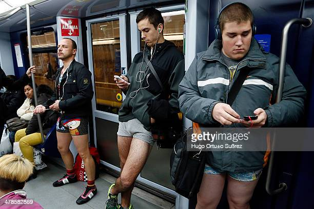 CONTENT] MADRID MADRID SPAIN JANUARY 12 Three men hold their smartphones in hand while traveling by subway without pants Dozens of Spanish travelers...