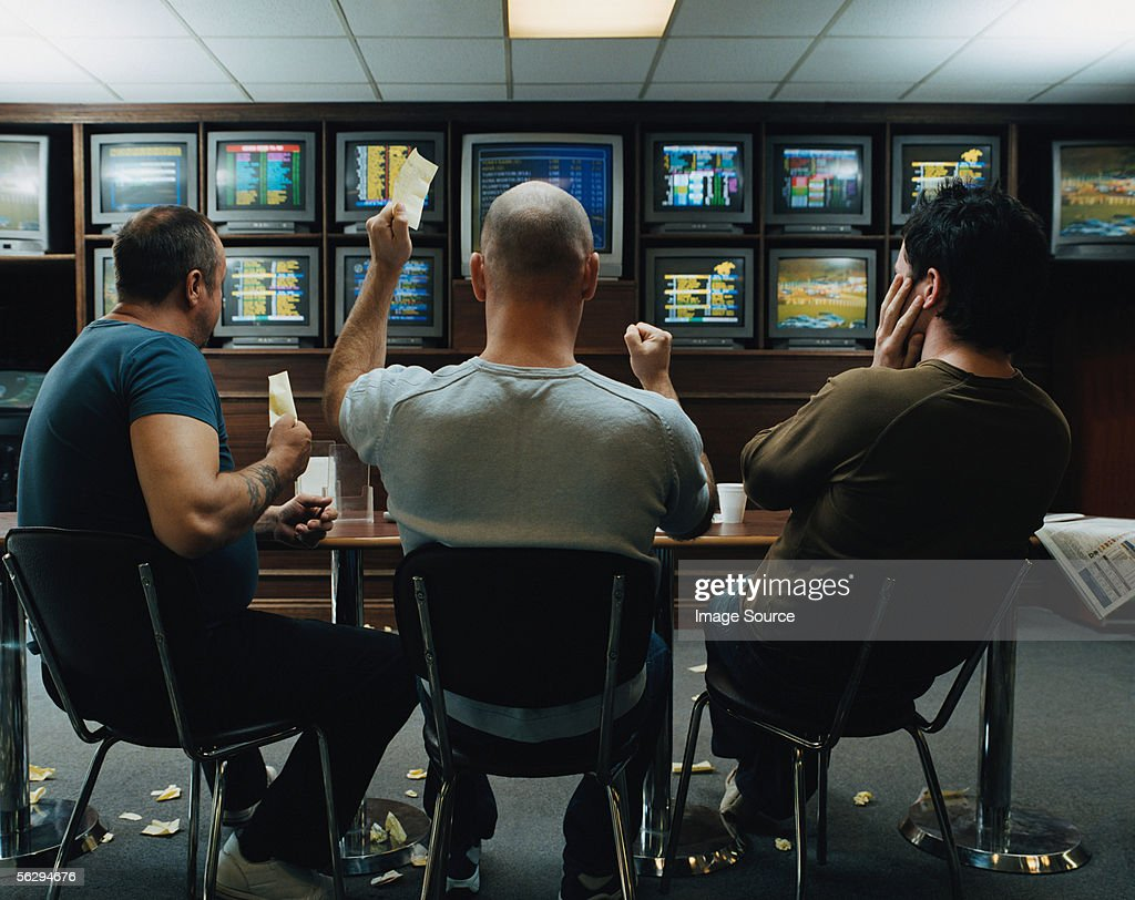 Three men in a betting shop : Stock Photo