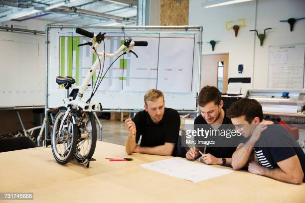Three men in a meeting at a bicycle factory, sitting at a table with a folding bicycle on the tabletop.