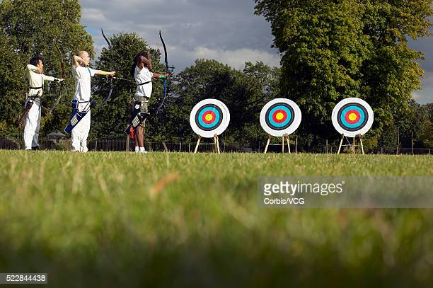 Three men in a row aiming their bows in an archery contest at three bull's-eyes