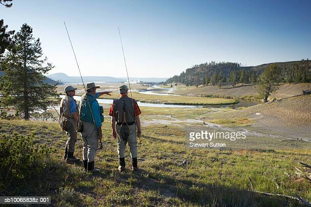 Three men in fishing vests looking at river, rear view