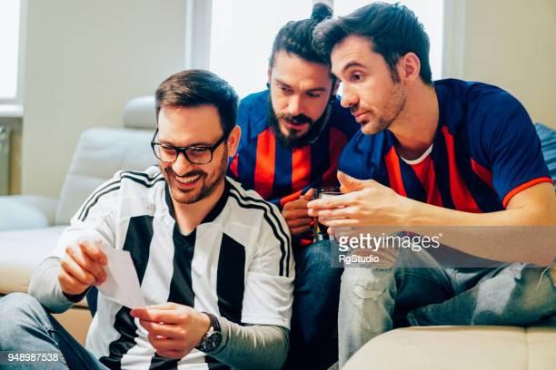 Drei Männer im Fußballtrikots Wettschein betrachten