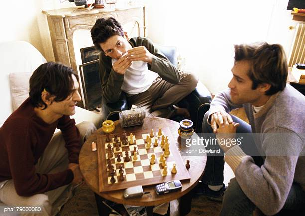 three men in living room, two playing chess - 若い男性だけ ストックフォトと画像