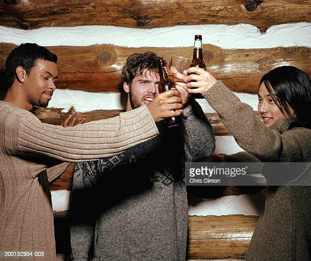 Three men in log cabin with alcoholic beverages toasting