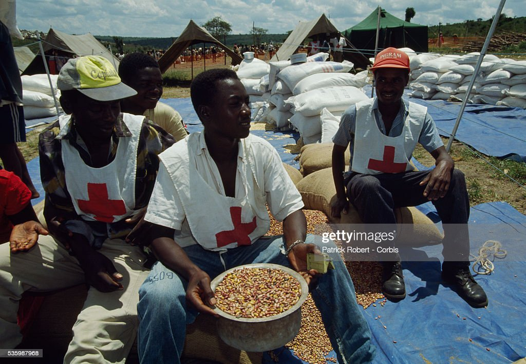 Three men in Red Cross vests sit with a supply of grain at Maza Refugee Camp in southern Rwanda. The camp run by Medecins Sans Frontieres was created for Hutu refugees escaping the inter-ethnic civil war in Rwanda. In April 1994, civil conflict broke out in Rwanda between Hutus and Tutsis, the two major ethnic groups in Burundi and Zaire, leading to widespread genocide in Rwanda.