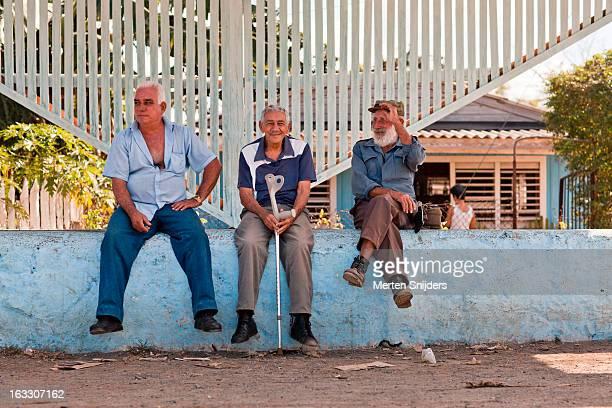 three men in shade on town square - merten snijders stock-fotos und bilder