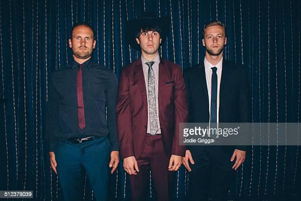 three men in suits standing together awkwardly - só homens jovens imagens e fotografias de stock