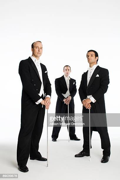 three men in tuxedos with canes