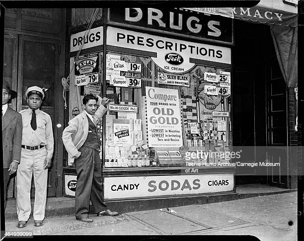 Three men, including man wearing uniform, and William W Goode standing outside of his Goode Pharmacy, with large advertisements in window for Old...