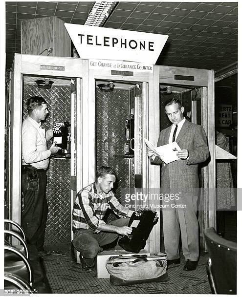 Three men install coin-operated pay telephones in an unidentified public space, Cincinnati, Ohio, early 1960s. The sign for a Hertz Rent a Car center...
