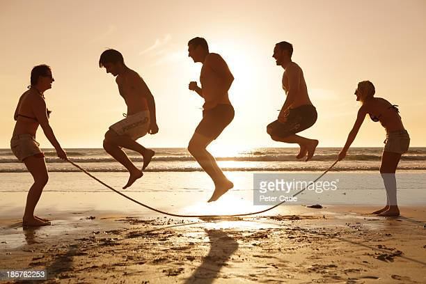 Three men jumping over skipping rope on beach