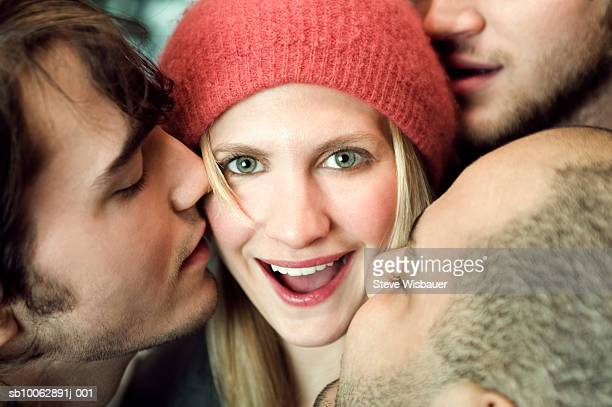 Three men kissing young woman, smiling, close-up