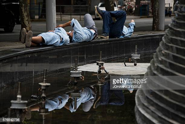 Three men lie next to a fountain in Shanghai on July 16 2016 China's secondquarter GDP growth was steady at 67 percent the government said as the...