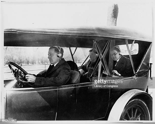 Three men listen to a radio in a car 1920s