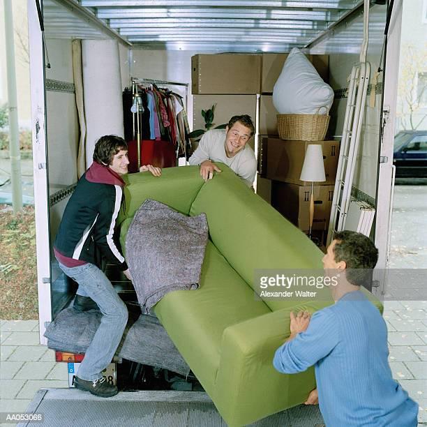Three men loading sofa into moving van