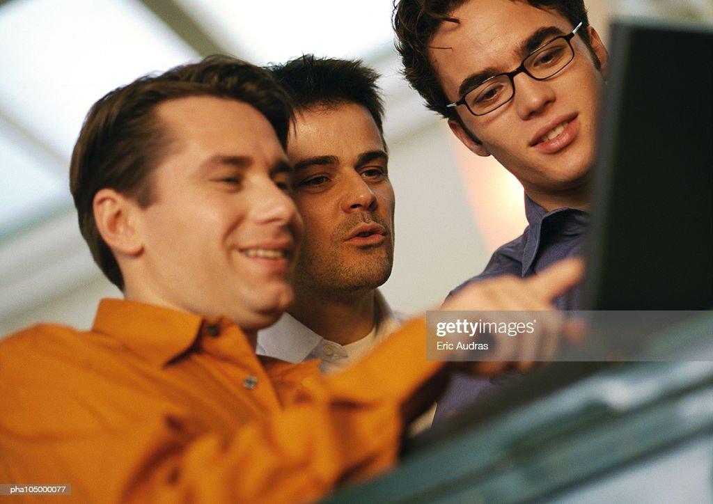 Three men looking at laptop : Stockfoto