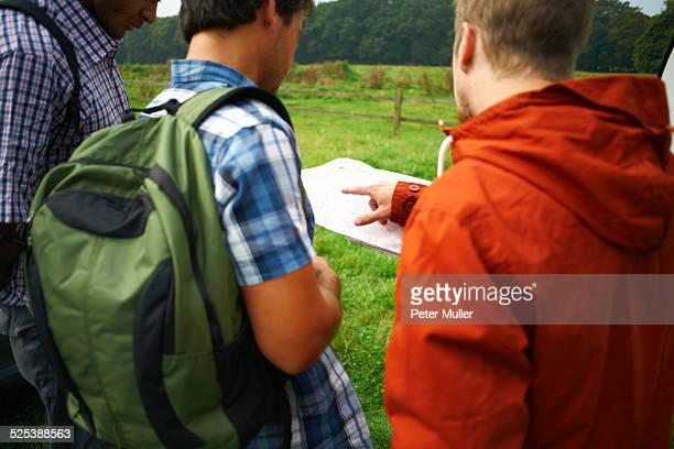 Three men looking at map