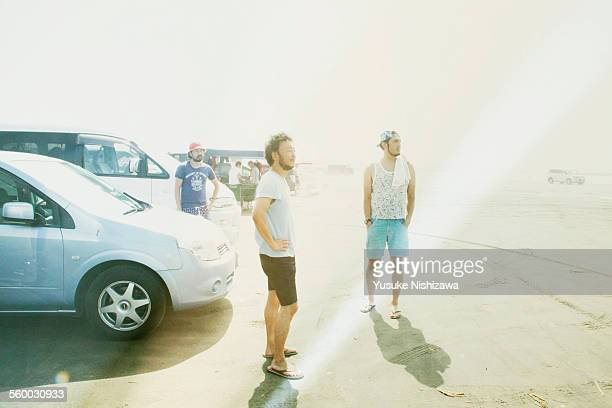three men looking at the sea - yusuke nishizawa stock pictures, royalty-free photos & images