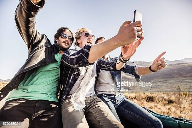 Three men on the road taking selfie in back of convertible, Franschhoek, South Africa