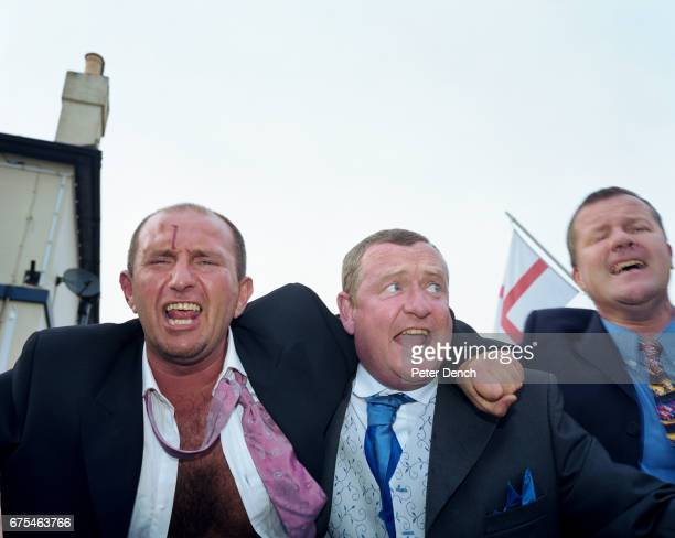 Three men one with a bloody head sing outside a pub next to Ascot Racecourse June 2002