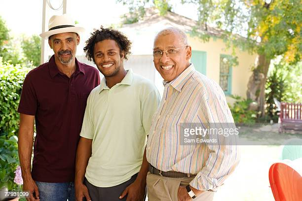 Three men outdoors on patio smiling