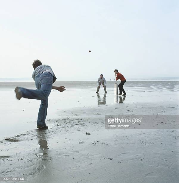 three men playing cricket on beach - wet t shirt contest ストックフォトと画像