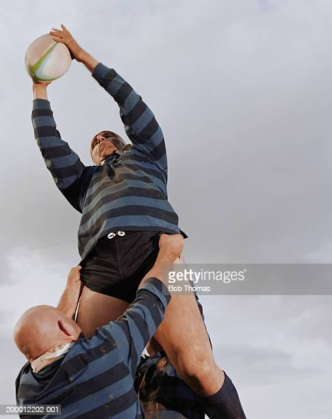 three men playing rugby, one being lifted by others in lineout - rugby union stock pictures, royalty-free photos & images