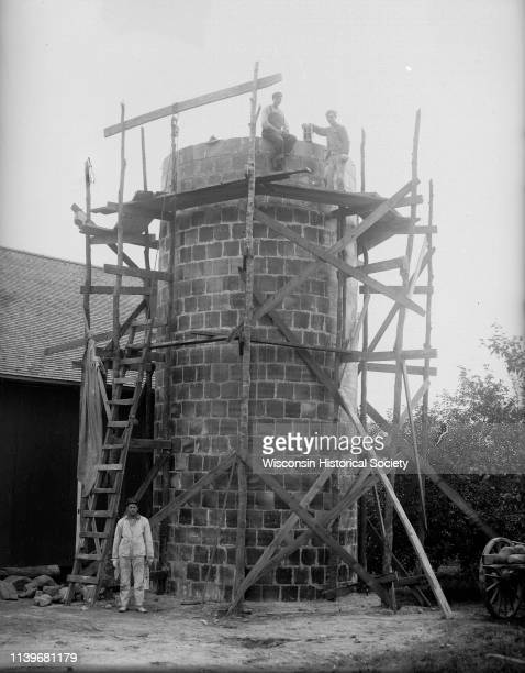 Three men pose next to a silo that is under construction with wood scaffolding around it Black River Falls Wisconsin 1900
