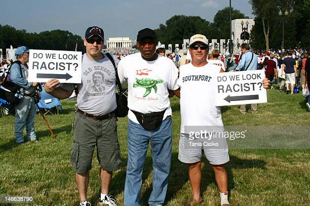 Three men posing during a rally at the Lincoln Memorial in Washington DC Two of the men are holding signs
