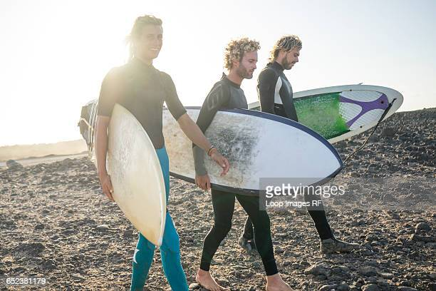 three men preparing to surf at corralejo in fuerteventura - atlantic islands stock pictures, royalty-free photos & images