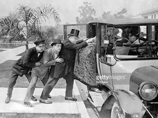 Three men pushing a stout woman into a car filled with children Undated movie still BPA2# 2989