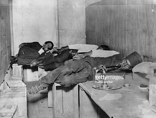 Three men relaxing and smoking opium
