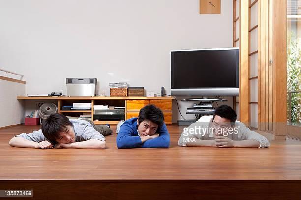 Three men relaxing on hardwood floor