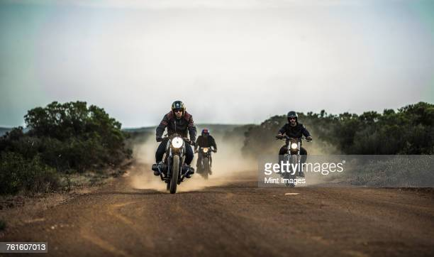 three men riding cafe racer motorcycles along dusty dirt road. - motorcycle biker stock pictures, royalty-free photos & images