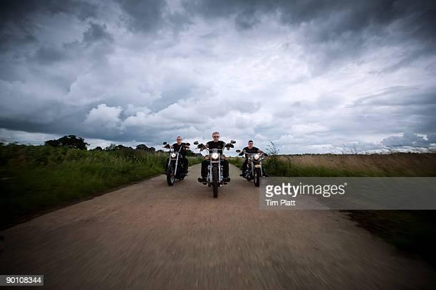 three men riding motorcycles. - のりものに乗る ストックフォトと画像