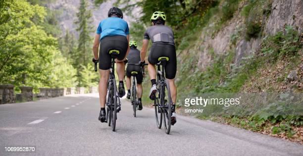 three men riding road bikes on mountain road - road cycling stock pictures, royalty-free photos & images