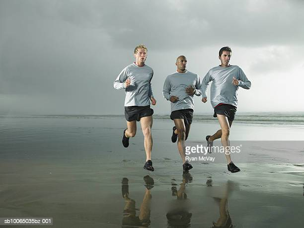 Three men running on beach by ocean
