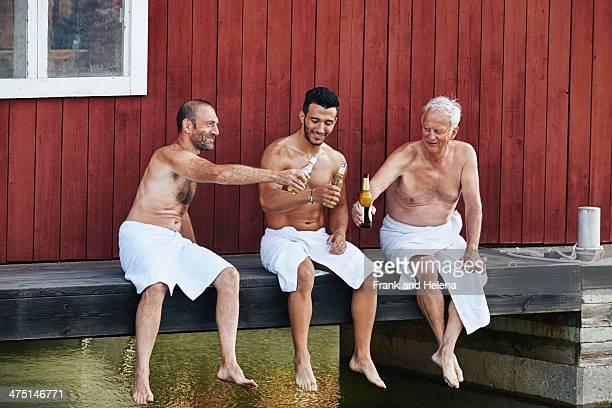 Three men sharing a beer outside sauna