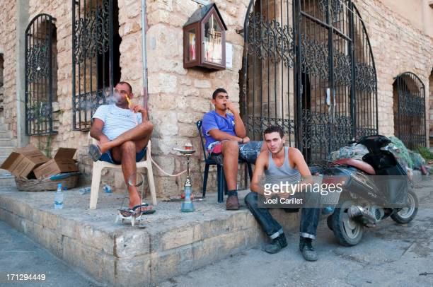 people sitting on a street corner in tyre, lebanon - lebanese ethnicity stock photos and pictures