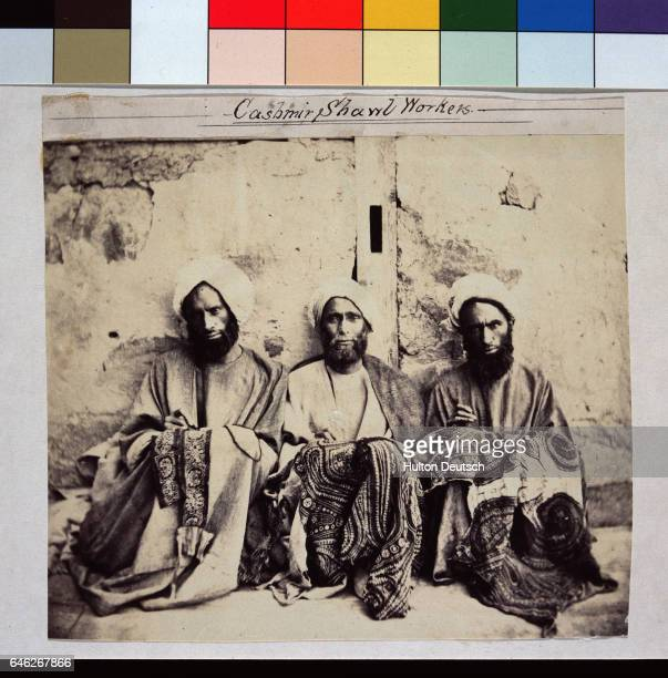 Three men sit on a sidewalk and embroider shawls India | Location State of Jammu and Kashmir India