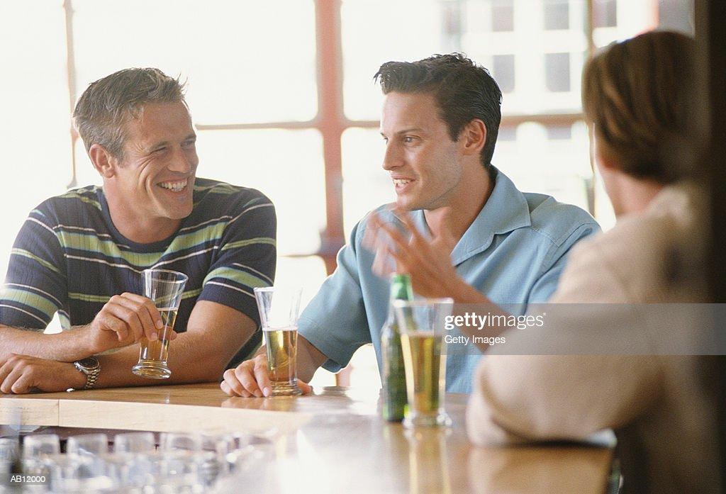 Three men sitting at bar having drinks : Stock Photo